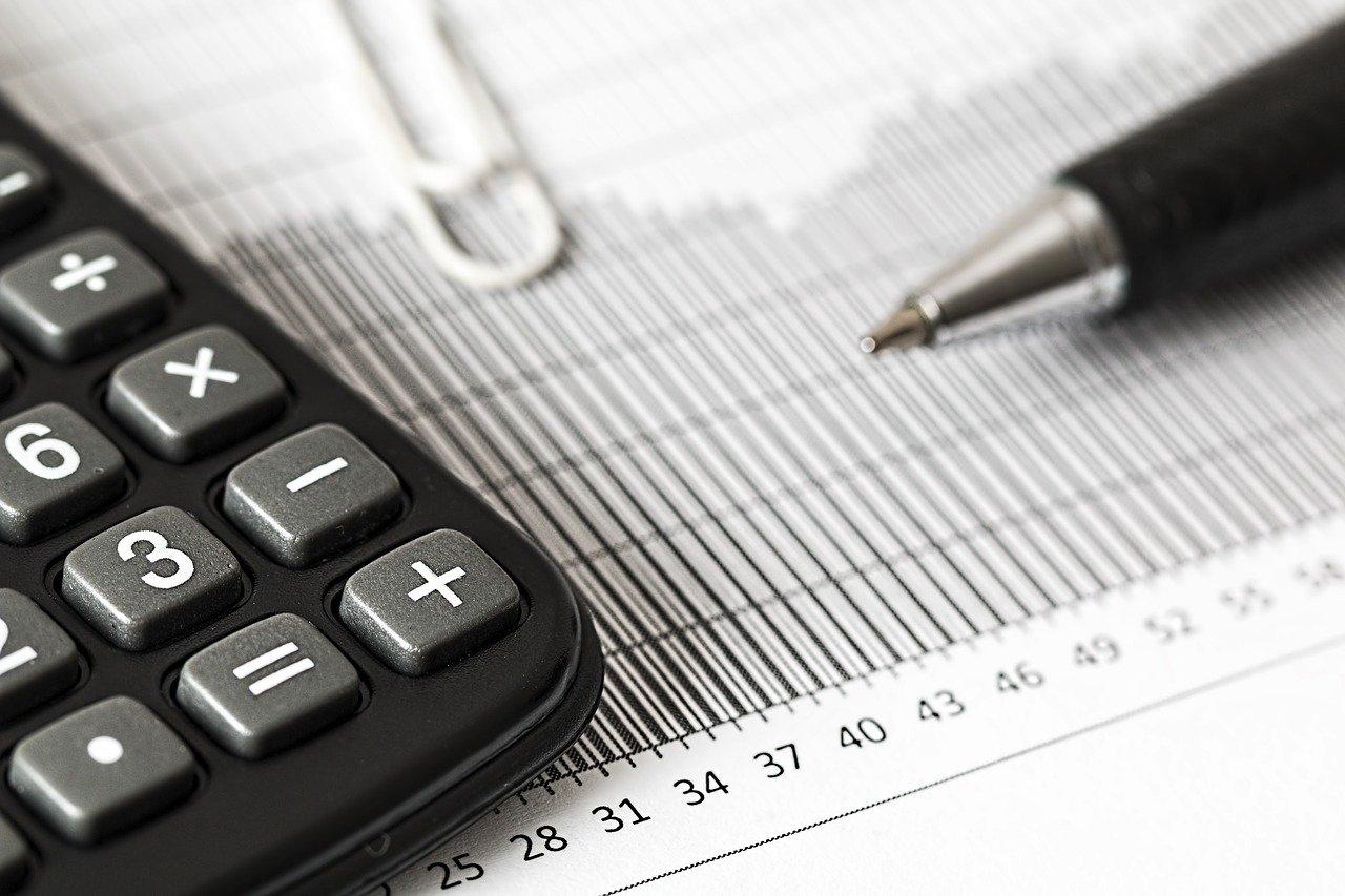 Imagem mostra uma calcularadora, papel e caneta