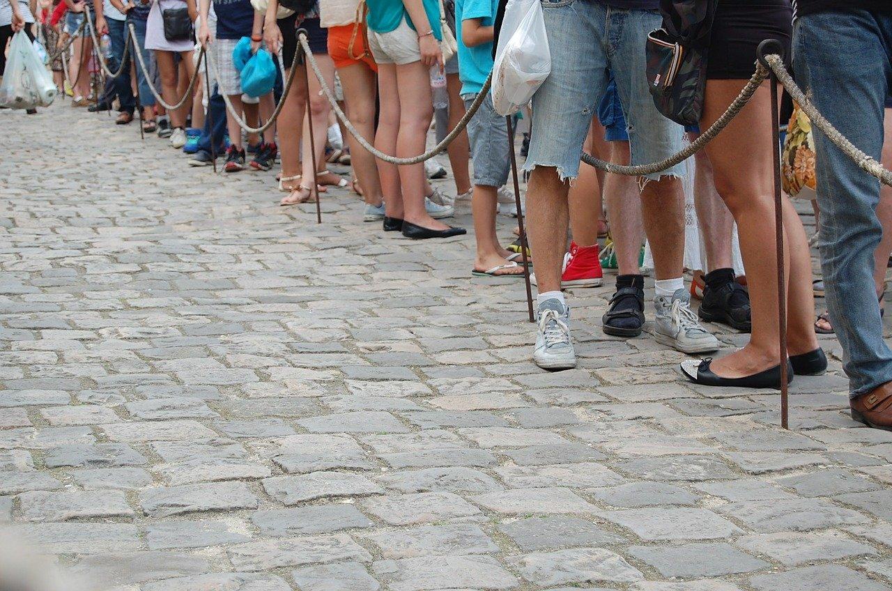imagem mostra pessoas em uma fila de espera. Agora, os fura-filas da vacina serão multados