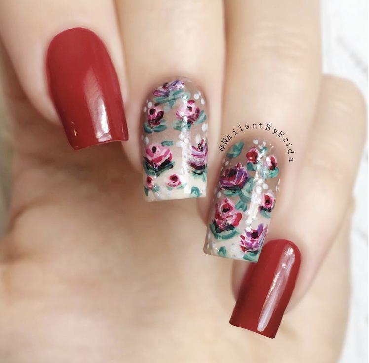 Unhas da mão com flores vermelhas delicadas