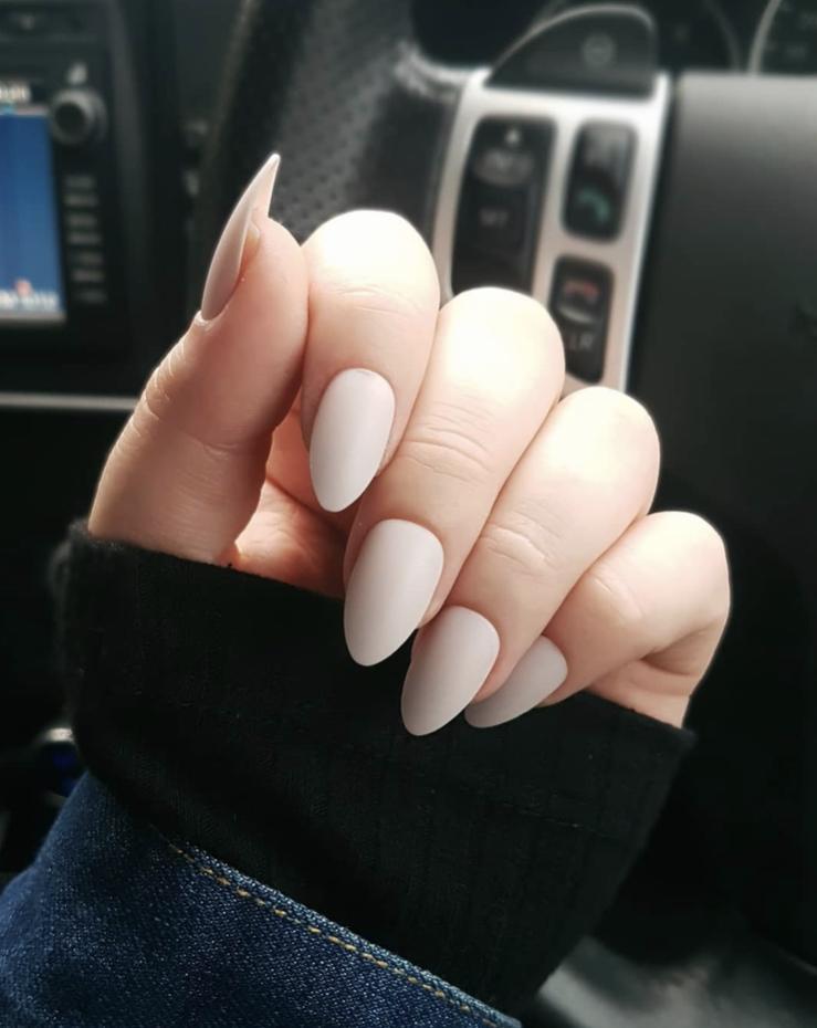 Unhas da mão pontudas e com uma coloração nude claro