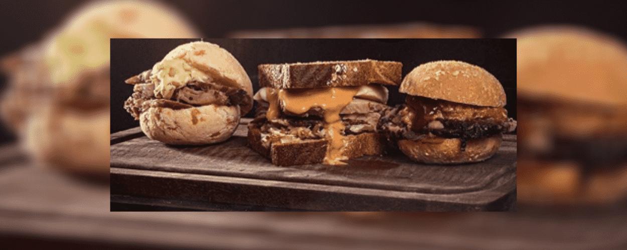 Três variedades de hambúrgueres artesanais expostas sobre tábua de madeira