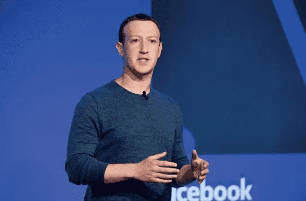 Foto mostra o milionário Mark Zuckerberg, homem branco, usando um suéter azul, em fundo azul.