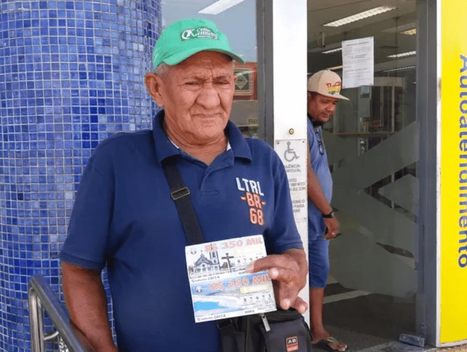 Foto mostra home idoso, de camisa azul, boné verde, com bilhetes de loteria na mão para vender.