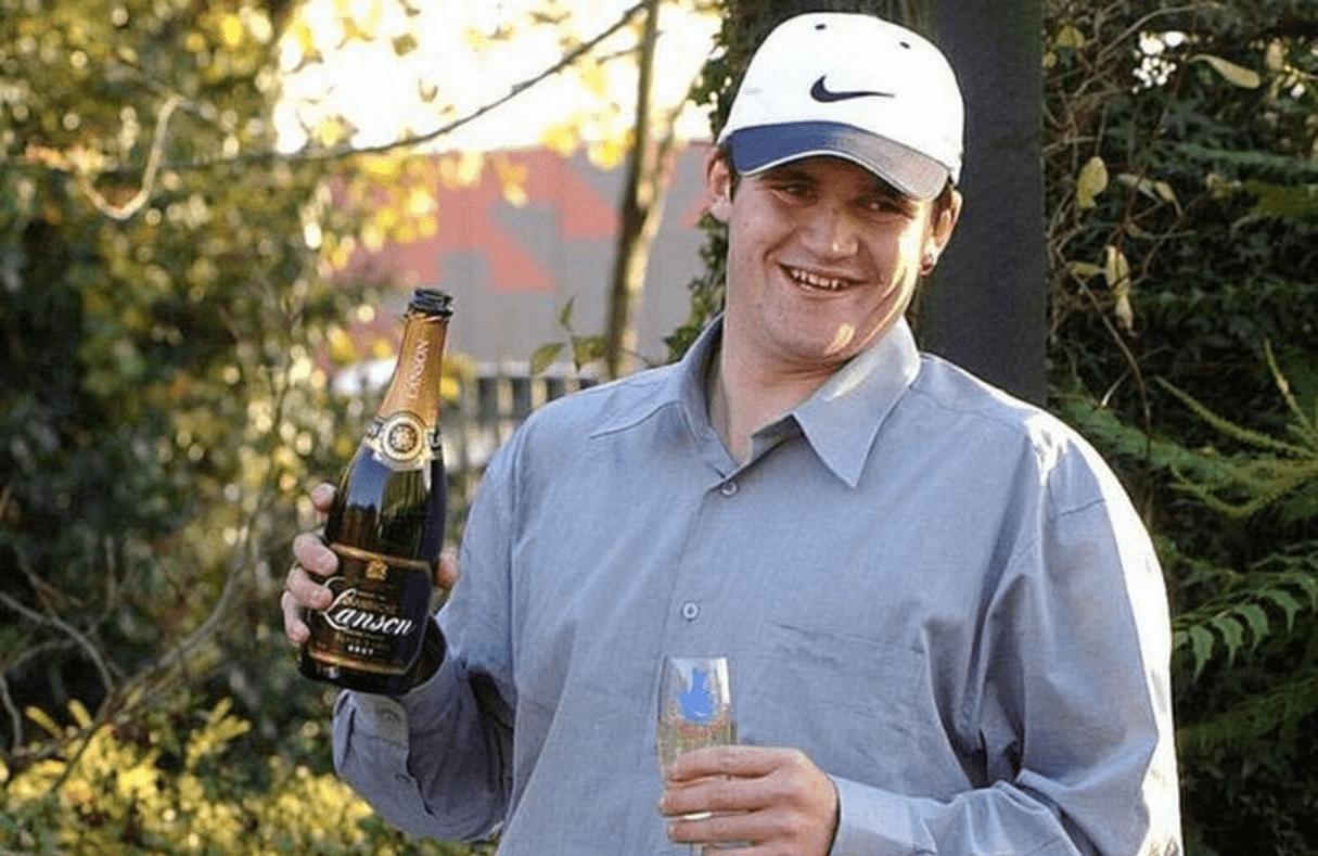 Foto mostra homem branco, de camisa social e boné branco. Segurando uma taça e uma garrafa de espumante ao ar livre.