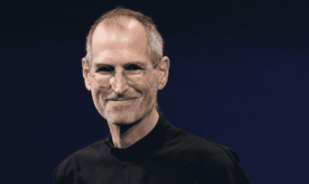 Foto de Steve Jobs, homem adulto, de cabelos grisalhos, usando óculos e uma roupa preta