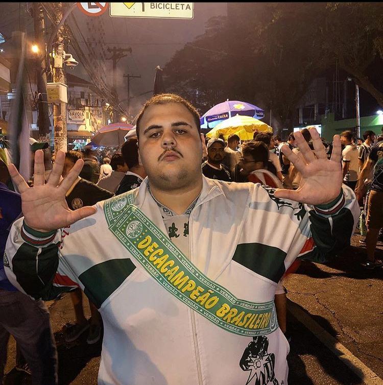 """Giovanni Tomoatti torcedor palmeirense na rua fazendo o sinal de 10 coma mão, no peito uma faixa escrito """"Decacampeão brasileiro"""""""