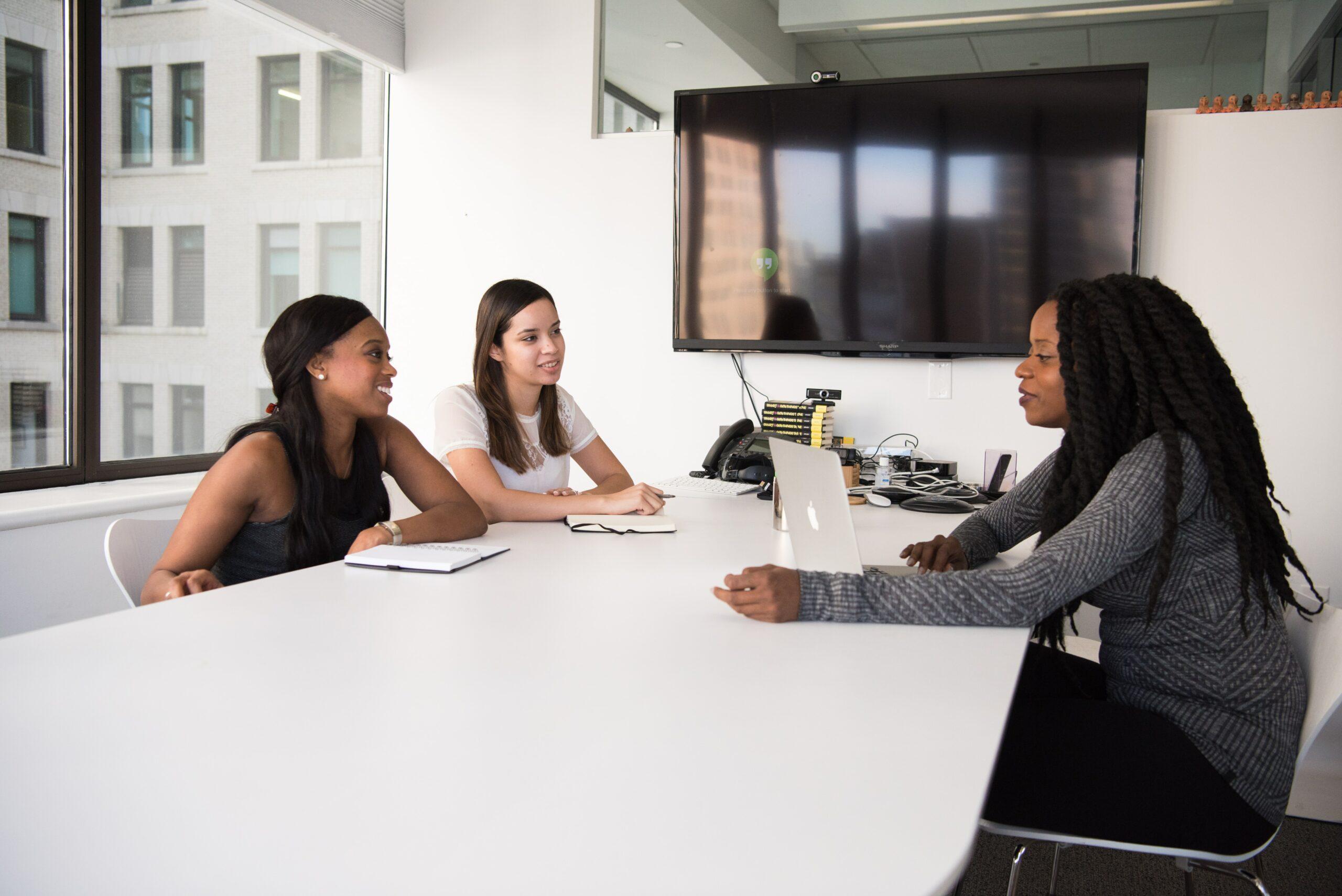Três mulheres sentadas em torno de uma mesa em um escritório