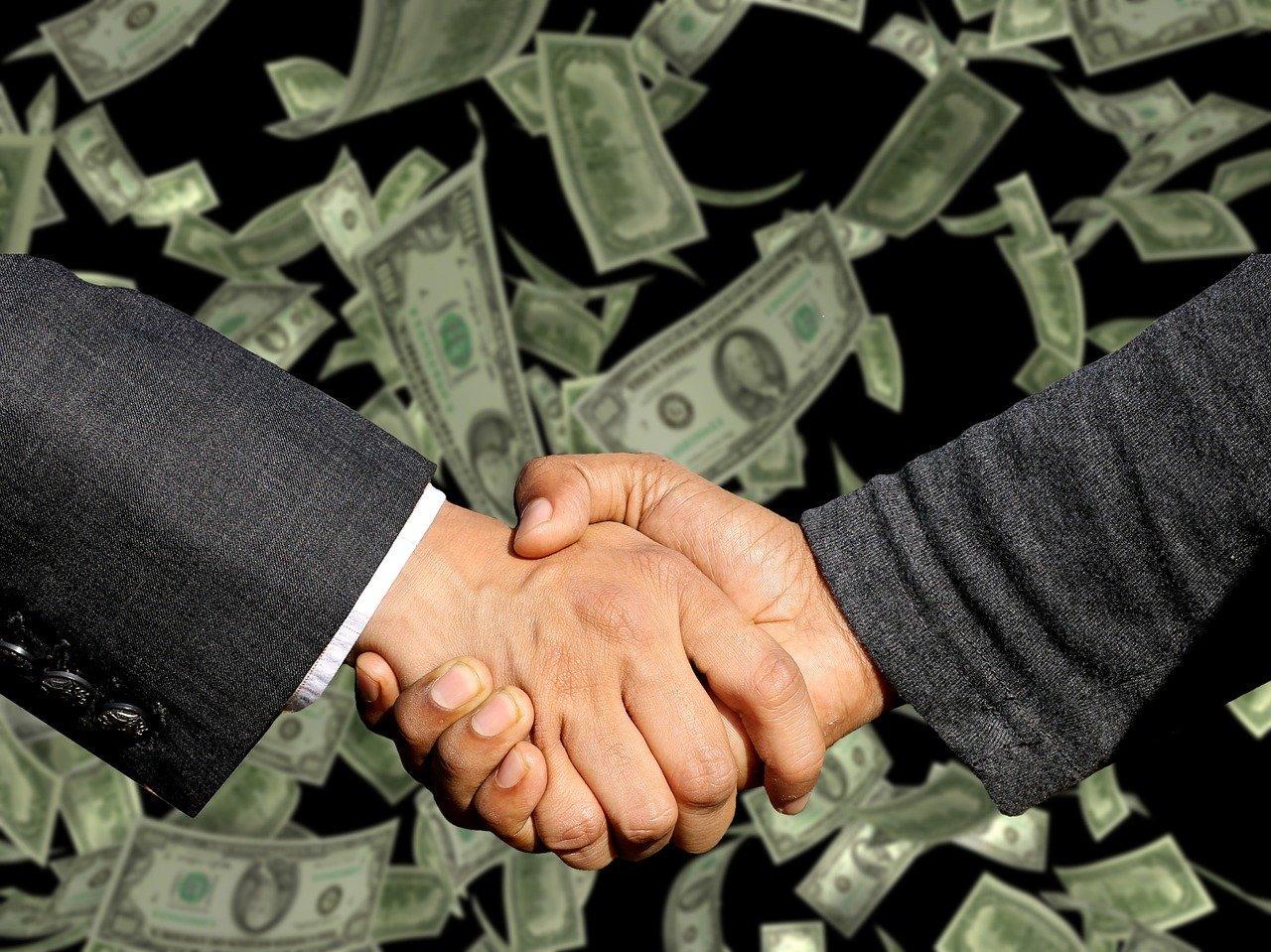 imagem mostra aperto de mãos com dinheiro atrás