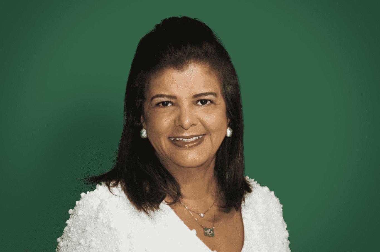 Foto de mulher adulta, com uma roupa branca em um fundo verde.