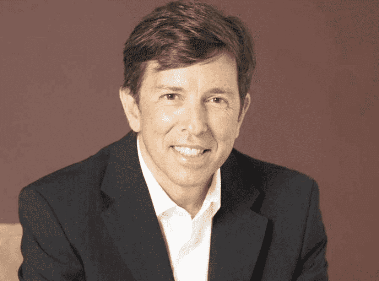 Foto mostra João Amoedo, do tronco para cima, sorrindo para câmera.