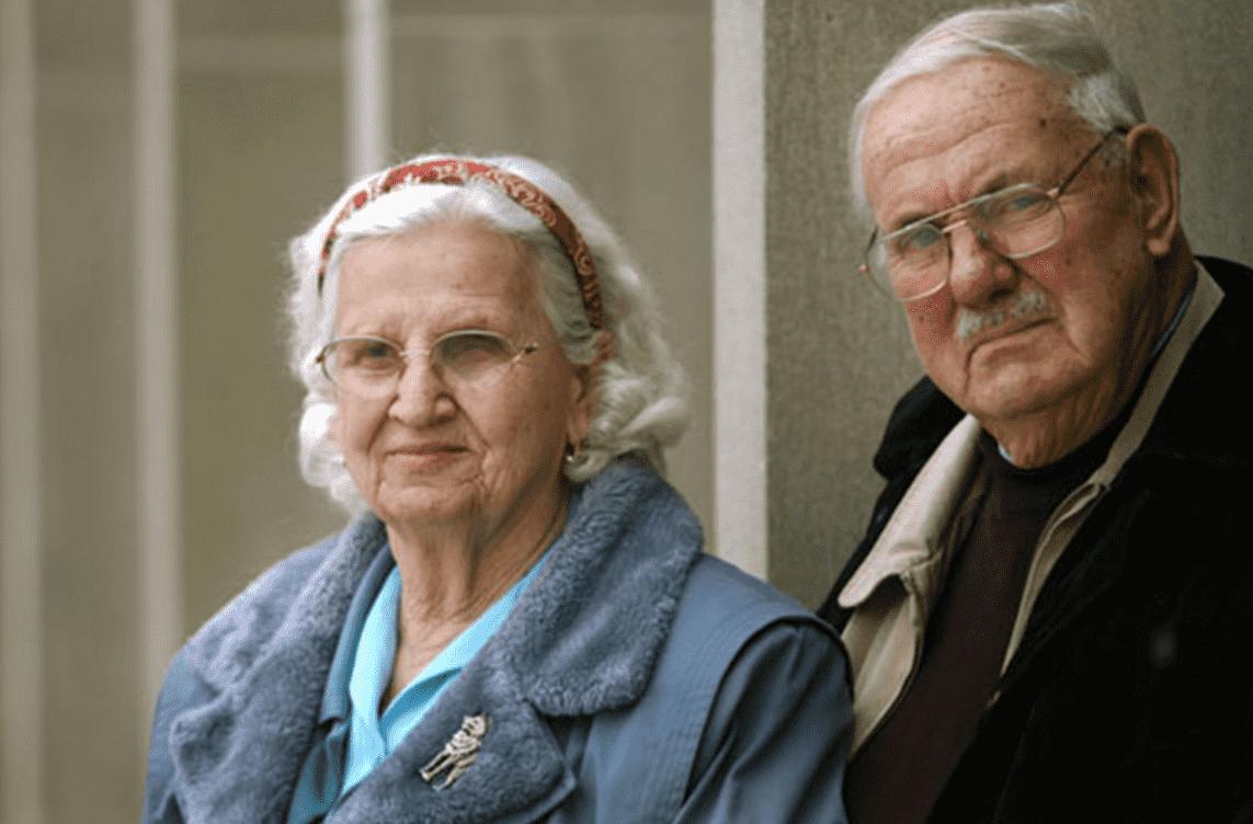 Imagem mostra Alex e Rhoda Toth, casal de idosos. Ambos tem cabelos brancos, e vestem casacos. O homem usa óculos e bigode.