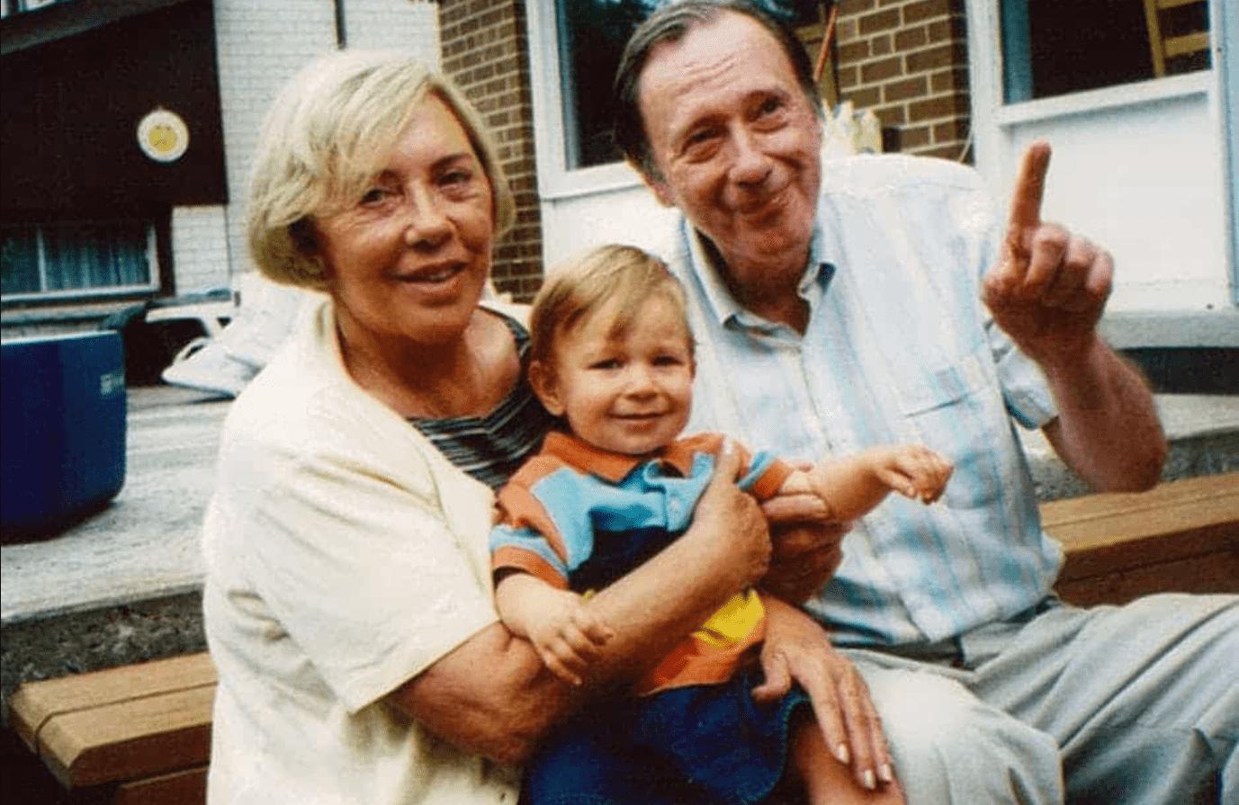 Foto mostra casal de idosos, sentados com uma criança no colo.