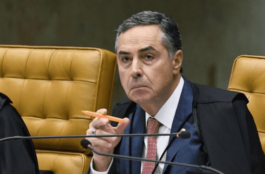 Foto mostra presidente do TSE, sentado, usando terno e segurando um marca texto.