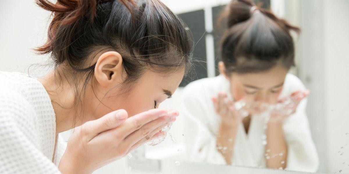 Mulher asiática com o rosto abaixado lavando o rosto