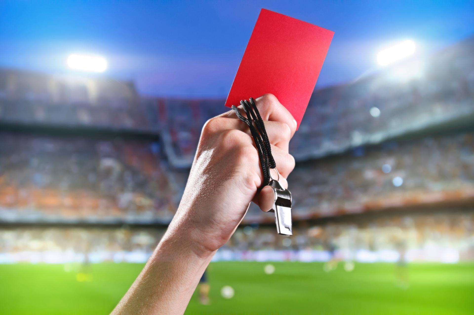 """""""Pra cego ver"""": na foto ilustrativa temos um foto não-verbal com um braço com um cartão vermelho à mão para jogadores suspensos"""