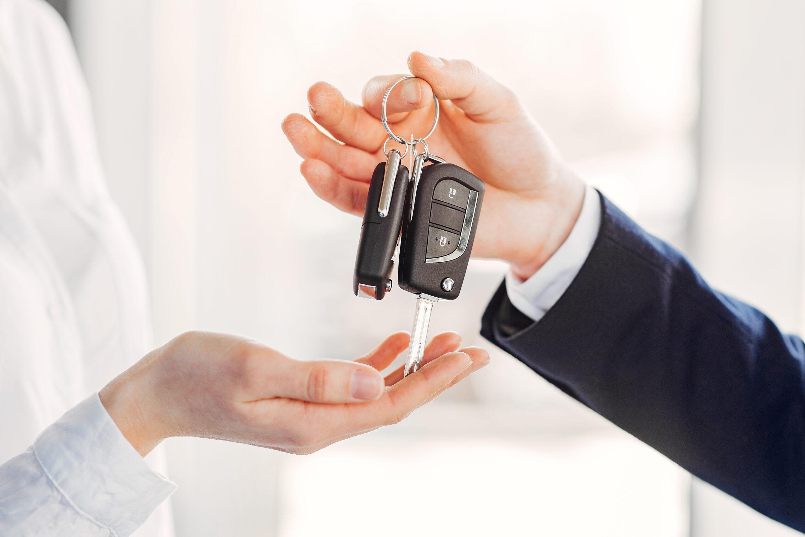 Pessoa entregando chave de carro barato para outra