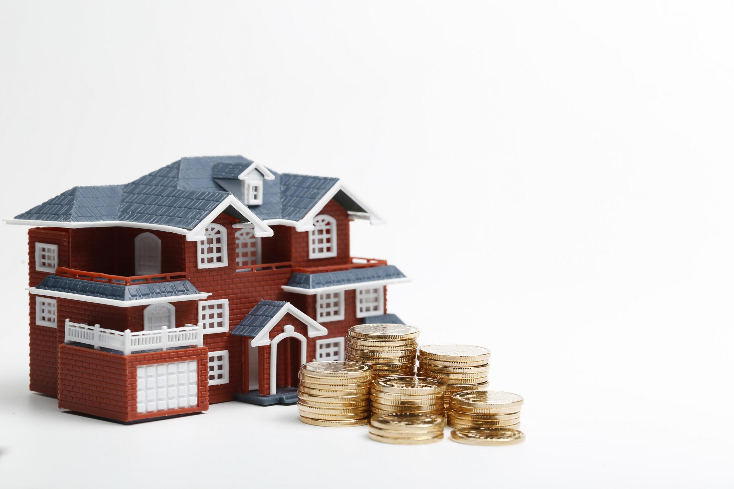 Casa de brinquedo e montante de moedas à frente
