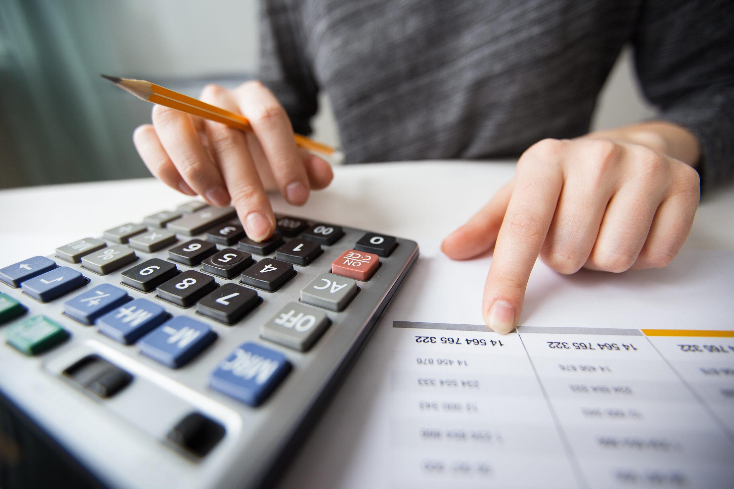 Pessoa com calculadora, lápis e papel