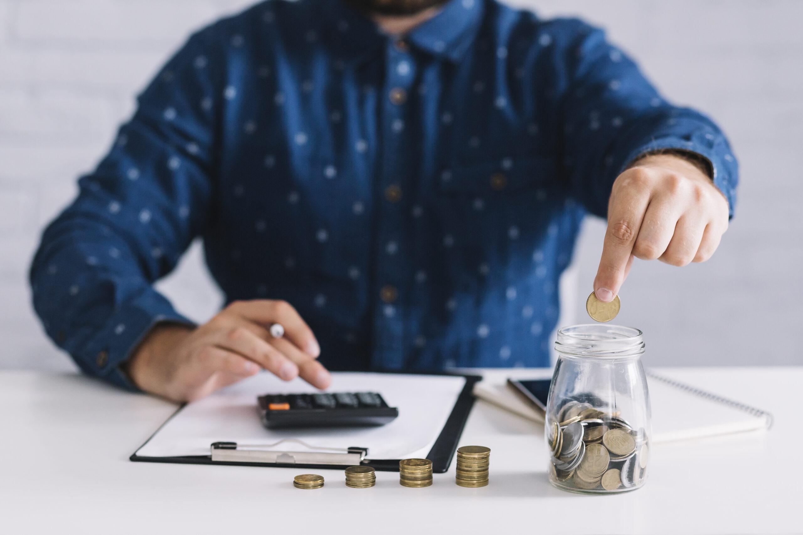 Homem calculando e inserido moedas em um pote