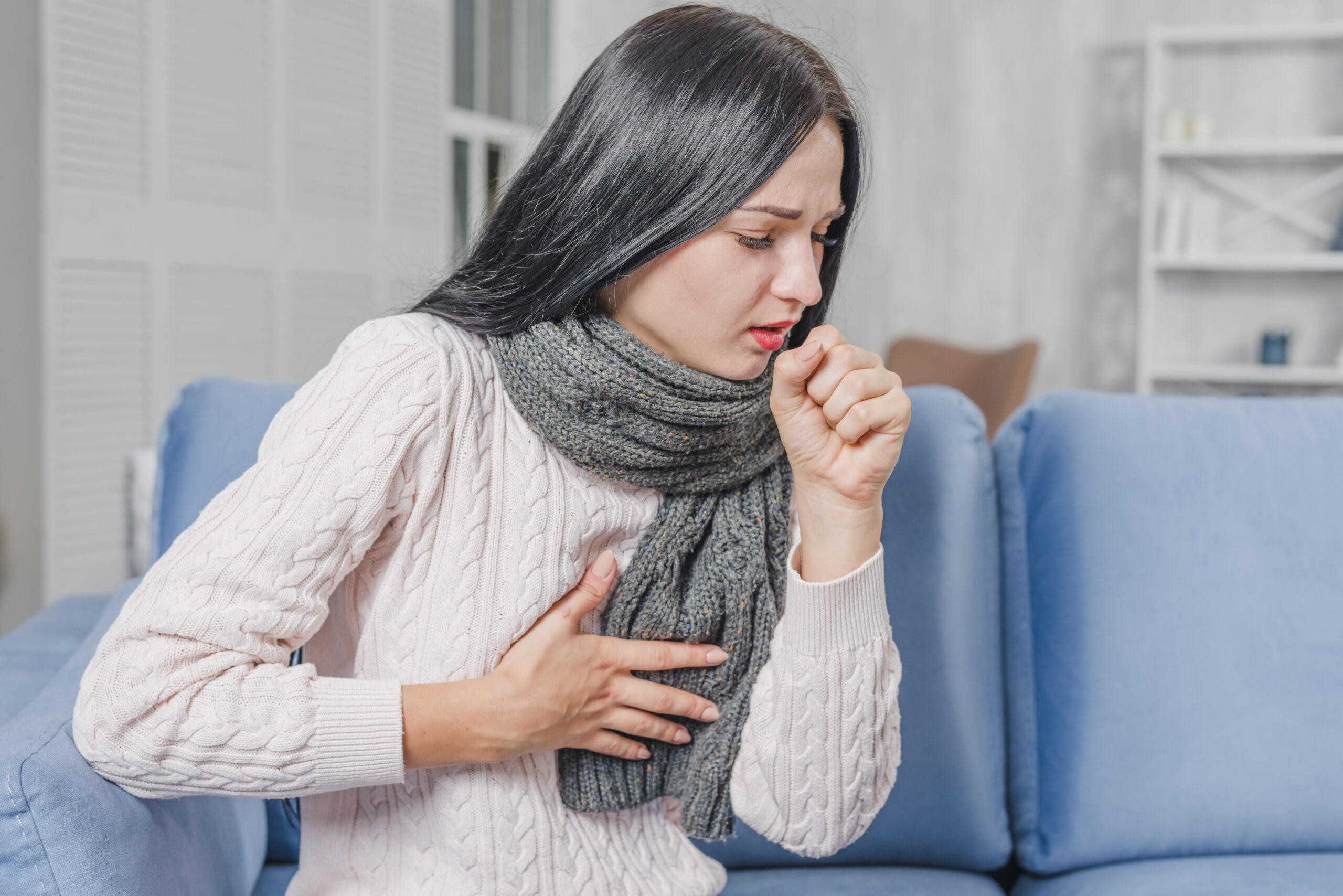 Jovem mulher sentada em um sofá azul, tossindo com uma mão sobre o peito