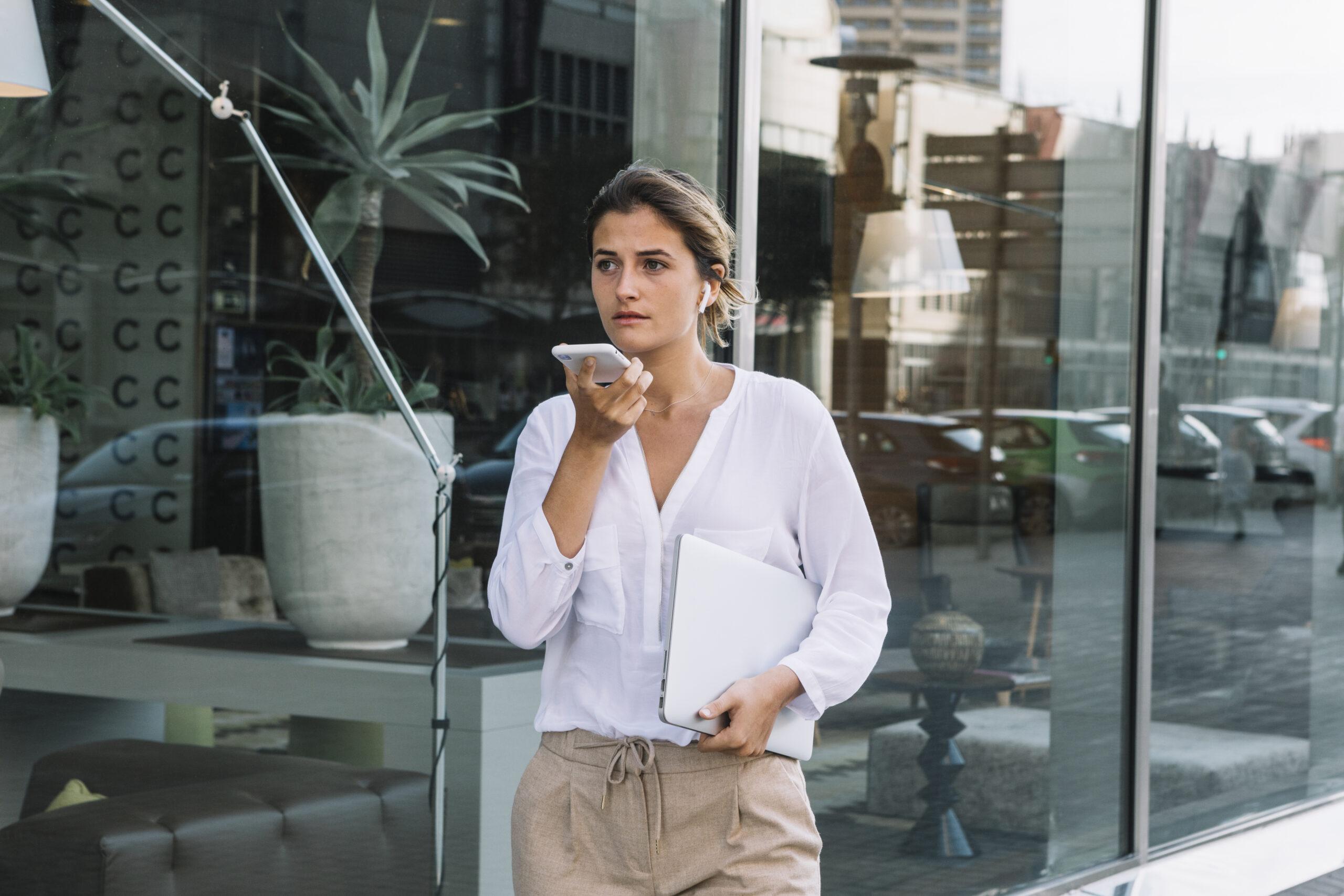 Mulher jovem em frente a edifício usando comando voz