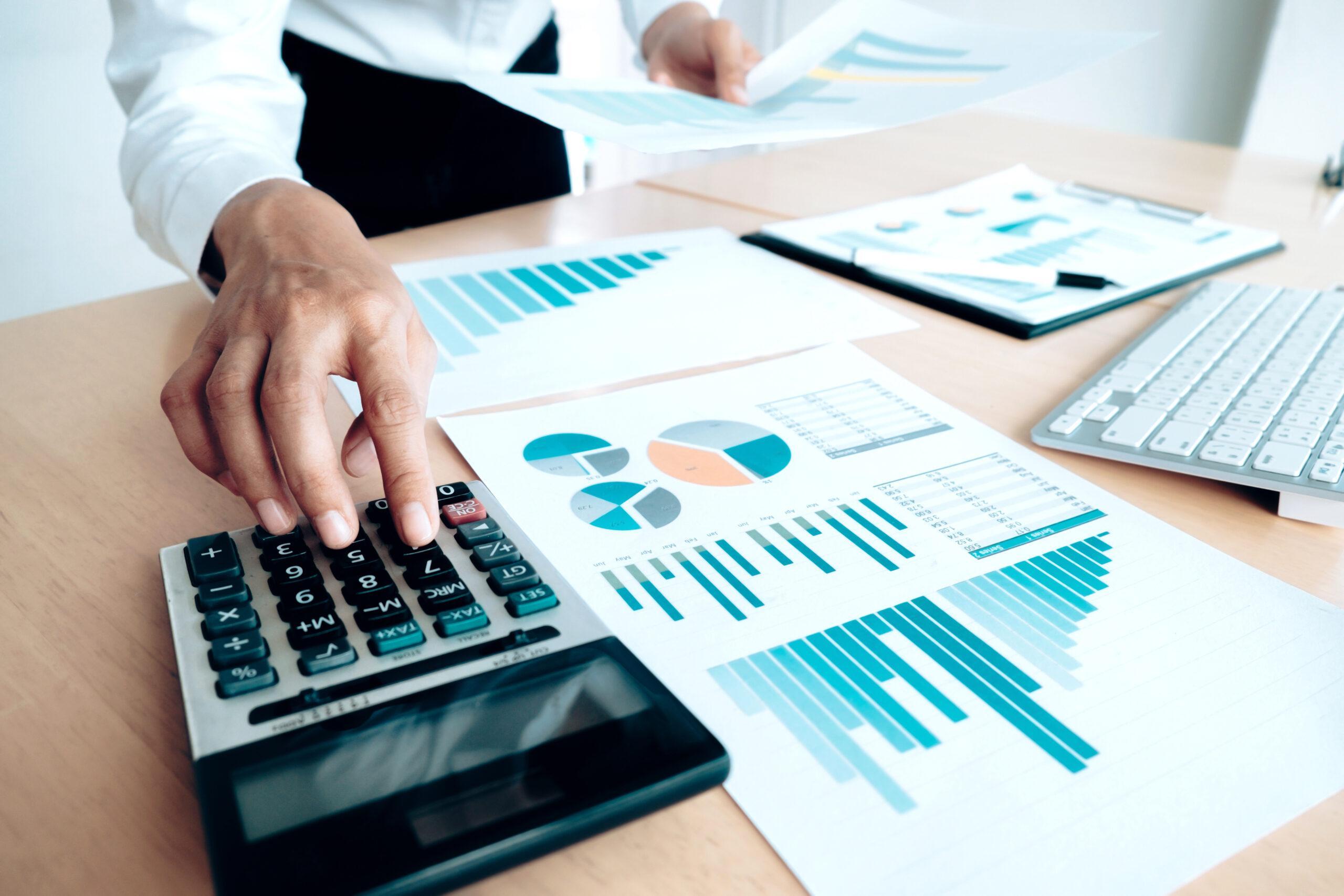 Uma mão fazendo uso de uma calculadora ao conta esquerdo da foto. Ao lado da calculadora, papéis com gráficos em barras e pizza coloridas
