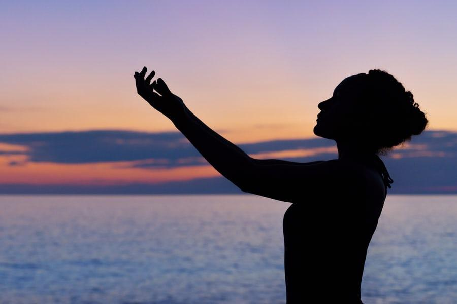 Uma pessoa em frente ao mar com as mãos para cima orando à Deus