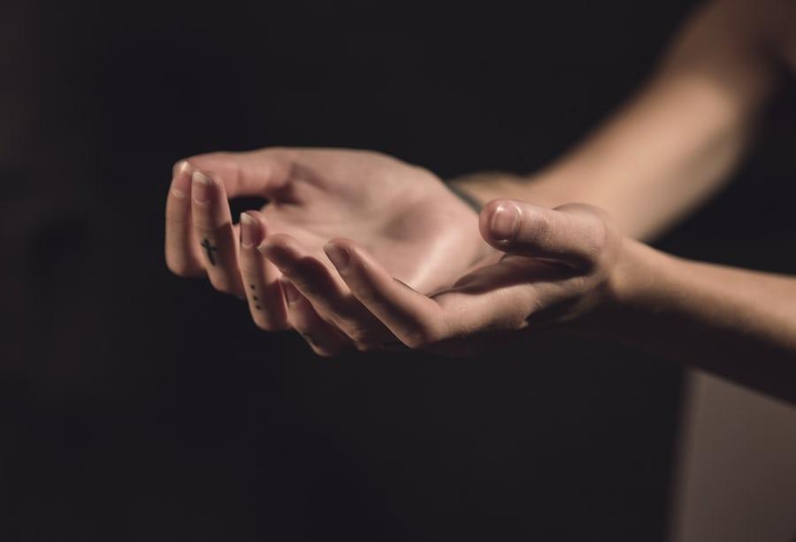 Mãos de uma pessoa para cima orando