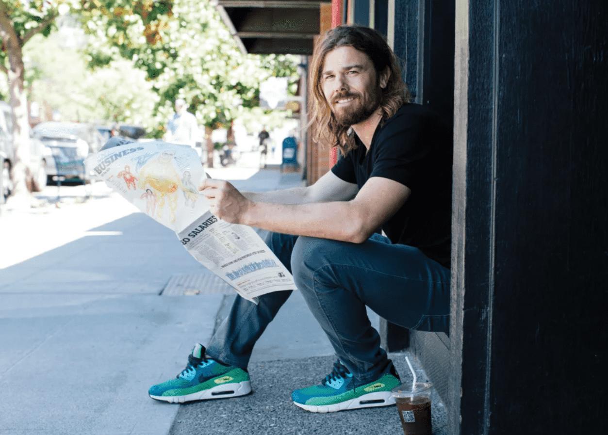 Foto mostra Dan Price sentado em um degrau, de lado, com um jornal nas mãos.