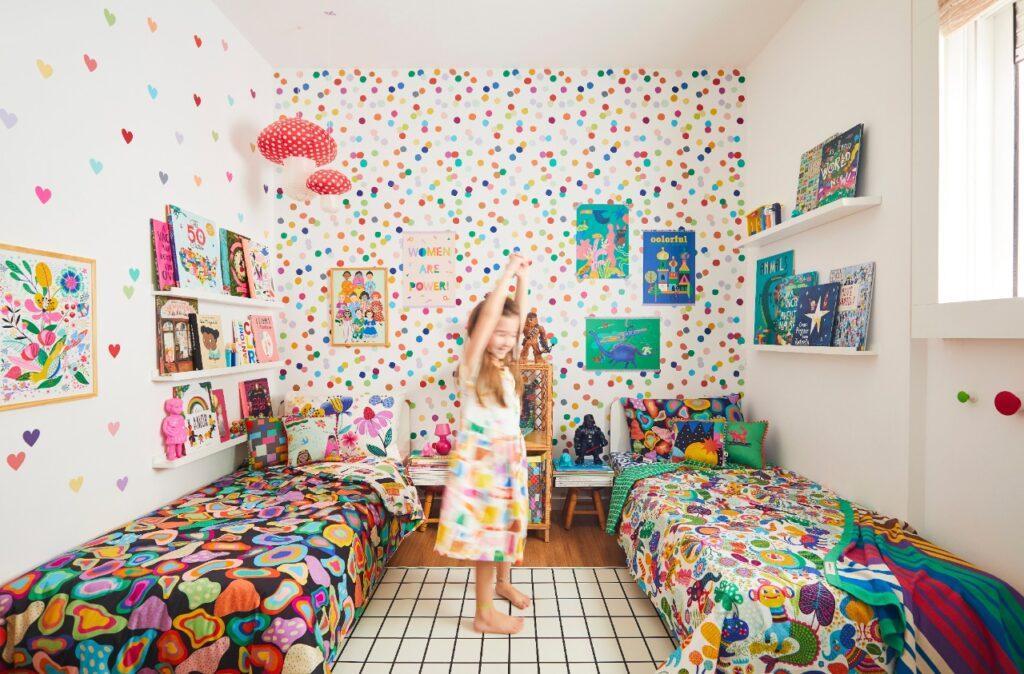 crianças brincam no centro de seu quarto colorido entre duas camas e em frente a um papel de parede de confete