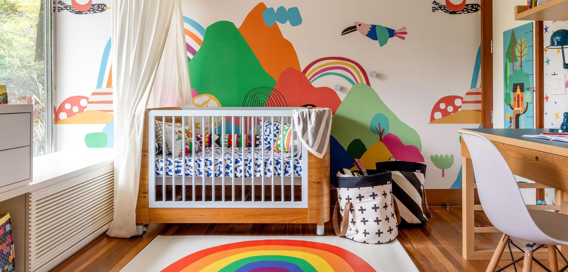 berço de bebê com roupa de cama colorida em frente a um papel de parede colorido de montanhas e passados.