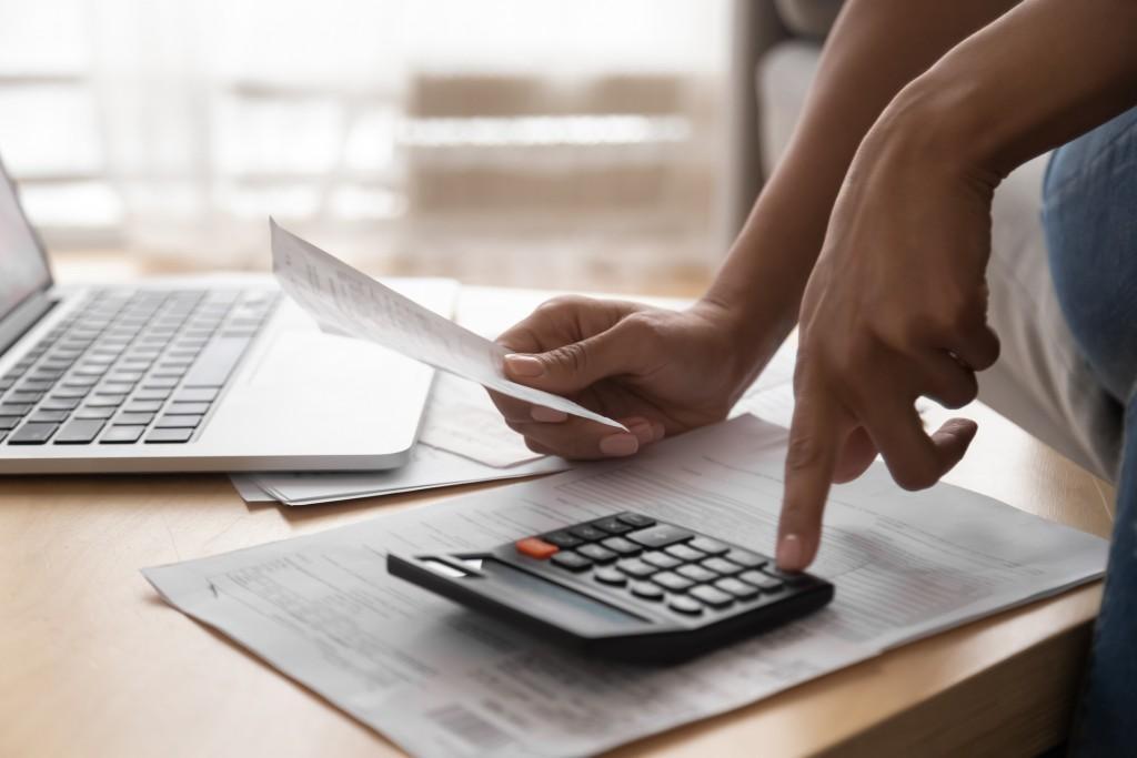 homem realiza cálculos na calculadora a partir de uma planilha