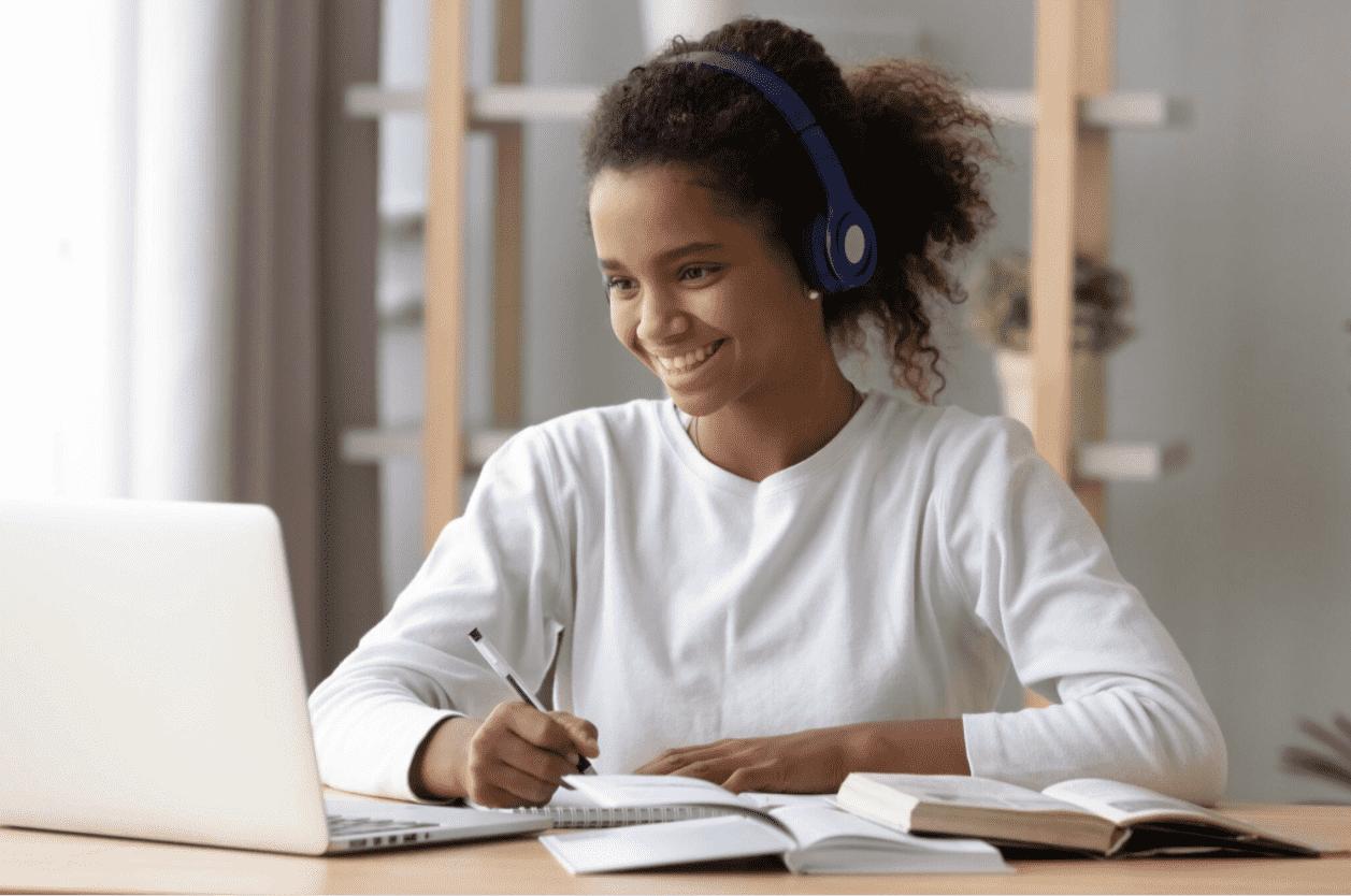 Foto mostra mulher sentada em frente ao computador e sorrindo para aprender inglês grátis