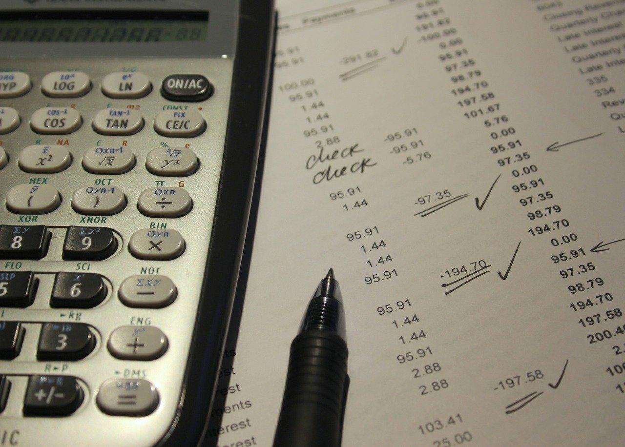 Calculadora em cima de papéis com números, ao lado de uma caneta