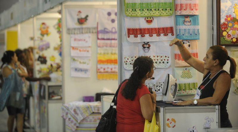 Foto mostra stands em uma feira de artesanato. Uma vendedora e uma cliente.