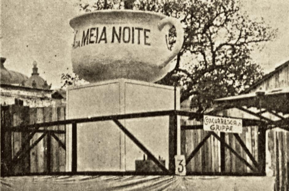 Foto do carnaval de 1929. Uma escola desfila com um xícara grande escrito meia noite.