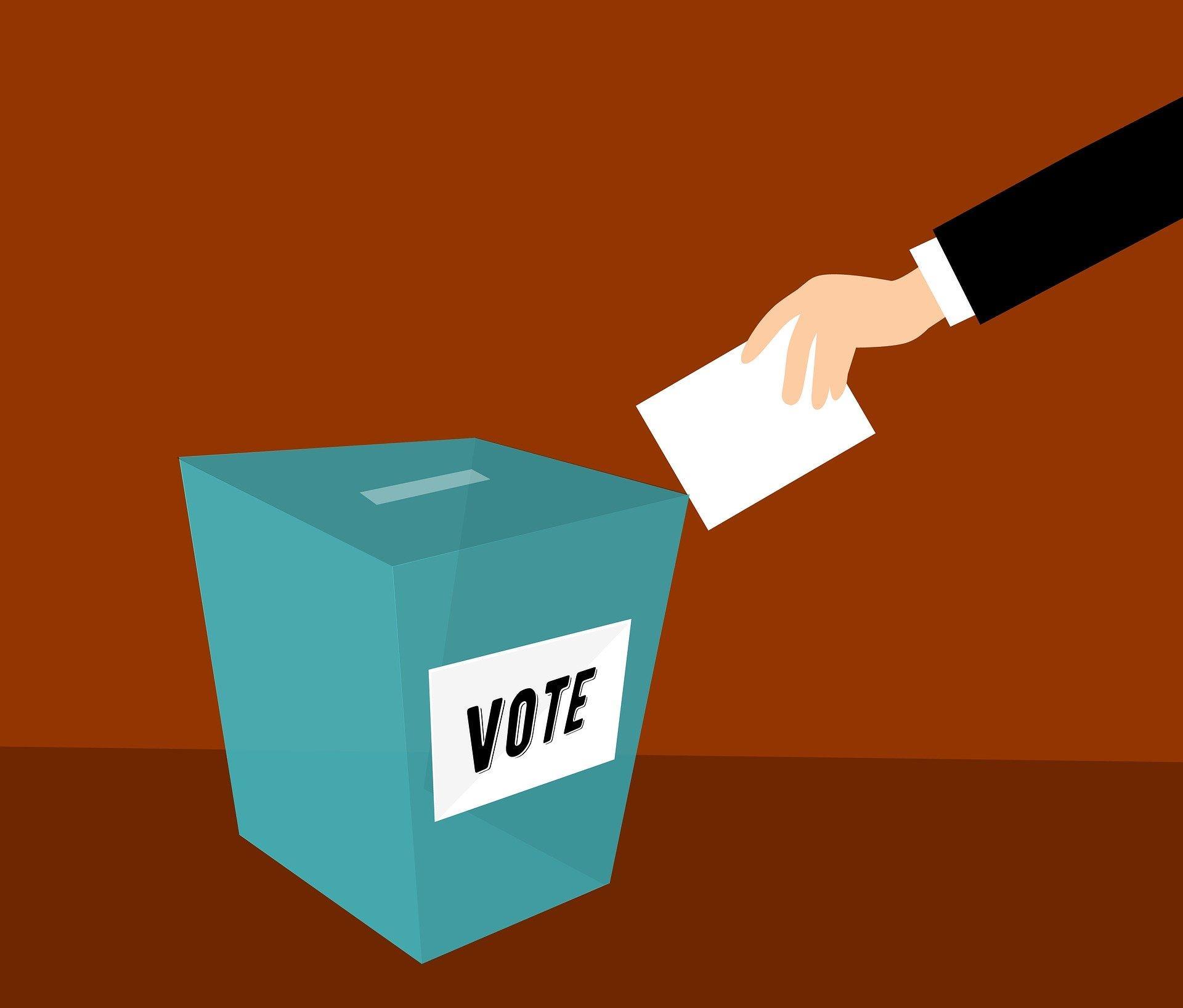 """urna azul escrito """"vote"""", voto em português, um braço esticado com o voto impresso em uma mão"""