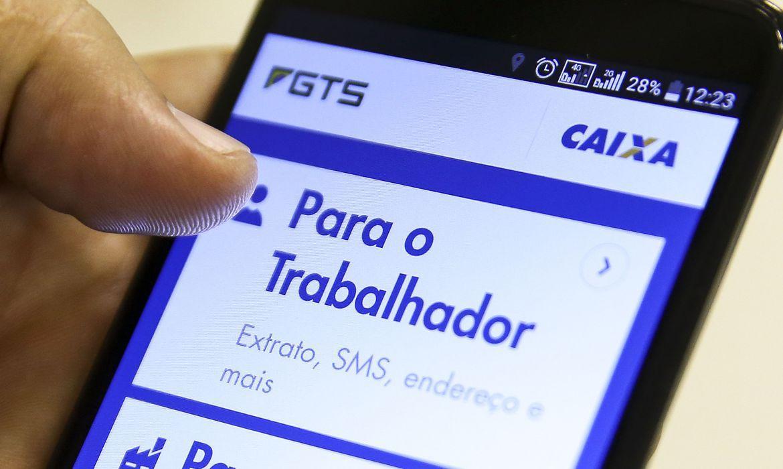 Imagem de mãos segurando o celular aberto no aplicativo FGTS da Caixa Econômica Federal