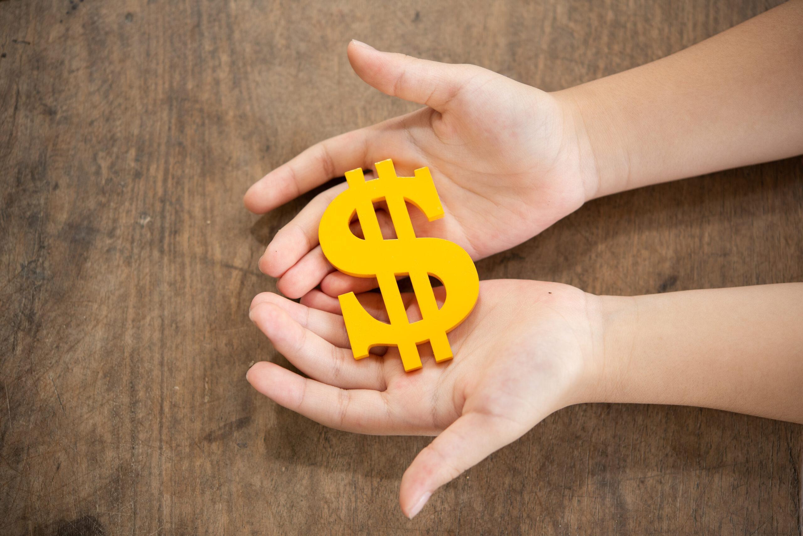 Mãos segurando um cifrão amarelo