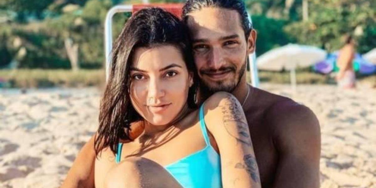 Gabi Prado e João Zoli sentados na praia olhando para frente