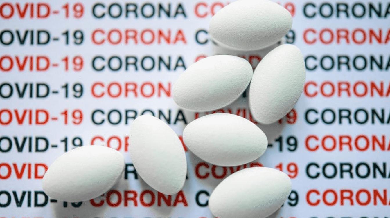 """Imagem mostra comprimidos brancos em cima de um fundo com a palavra """"COVID-19"""" escrita várias vezes."""