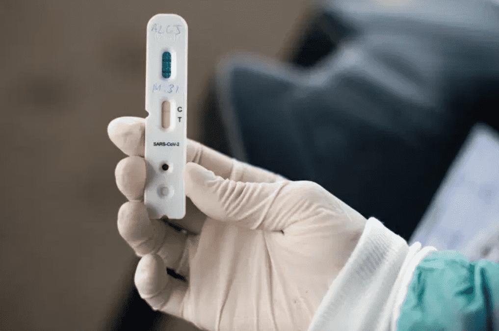 Foto mostra uma mão com luva segurando um teste rápido de coronavírus