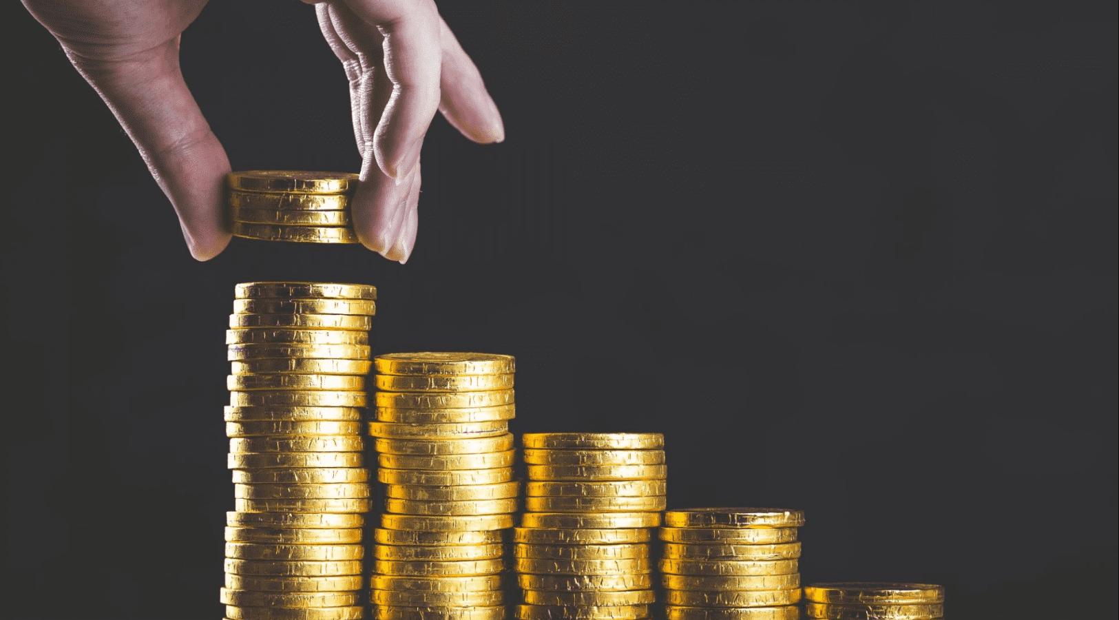 Imagem mostra ´pilhas de moedas e uma mão acrescentando outras.