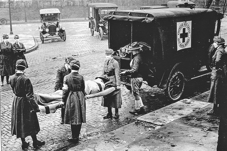 Foto antiga mostra soldados carregando outro soldado em uma maca para o colocar em uma ambulância.