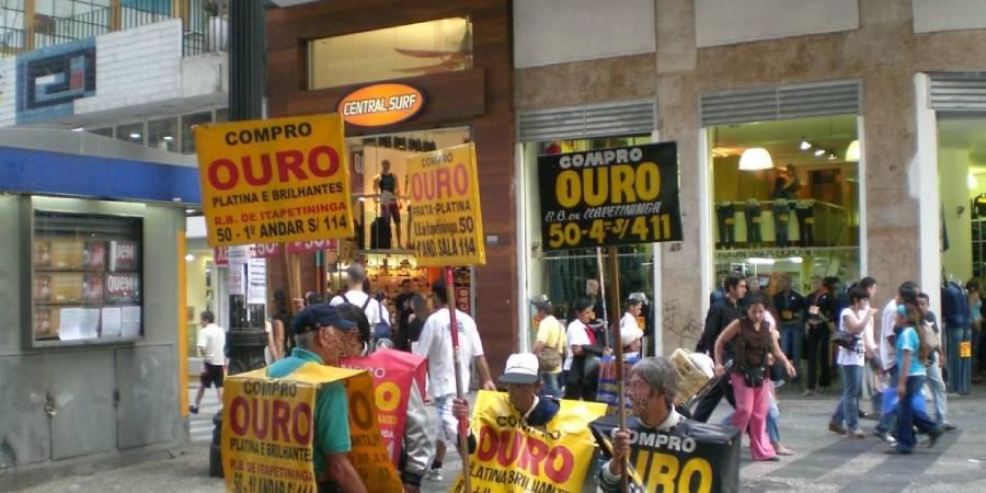pessoas segurando placa de compro ouro em rua comercial