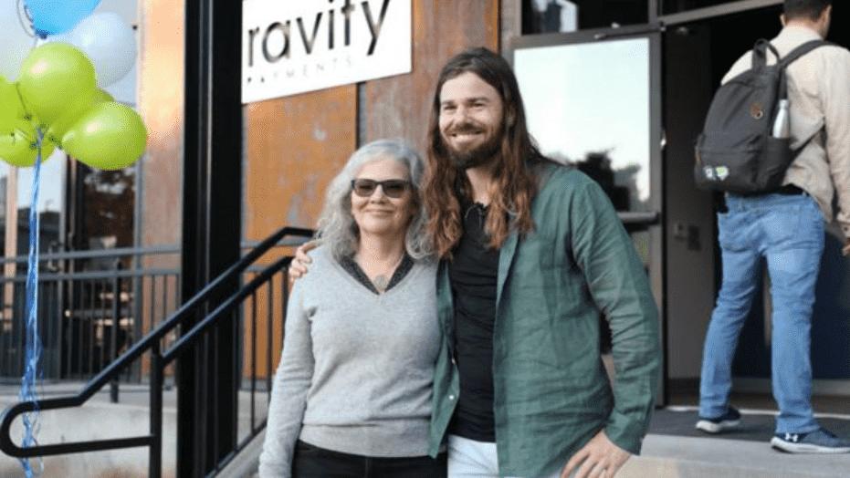 Foto mostra Dan Price abraçado com uma senhora, em frente à sua empresa.