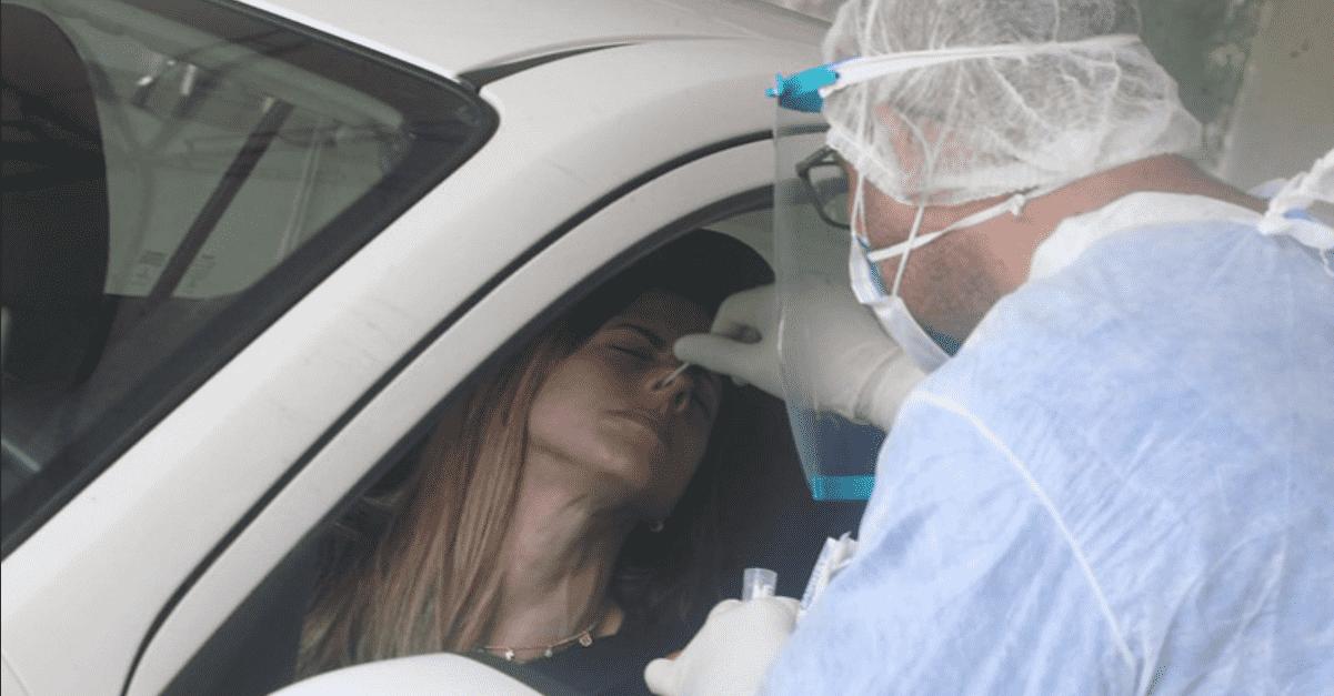 Foto mostra profissional coletando exame PCR de paciente dentro do carro.