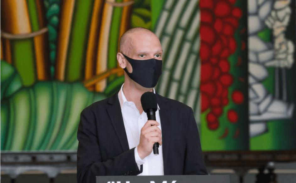 Foto mostra prefeito de São Paulo, Bruno Covas usando uma máscara e segurando um mcirofone.