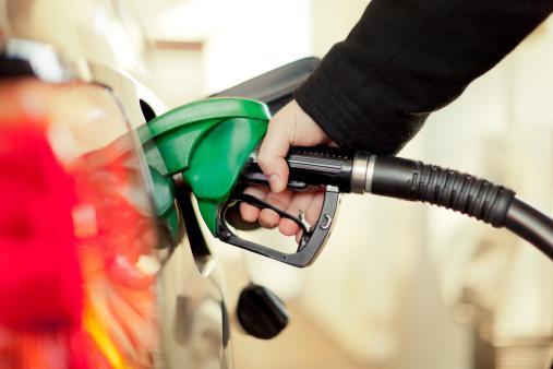 Uma mão coloca a pistola de gasolina no tanque para reabastecer o carro.