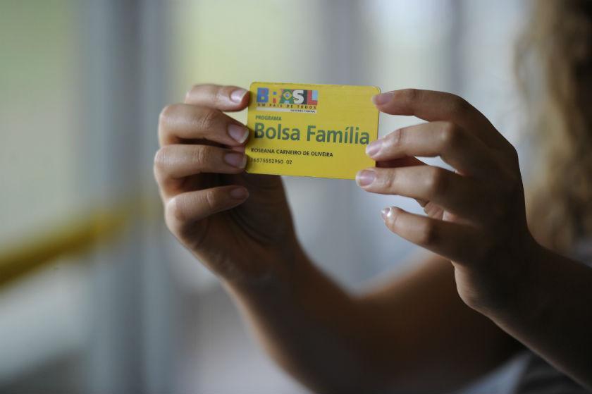 Duas mãos de mulher segurando o cartão do Bolsa Família